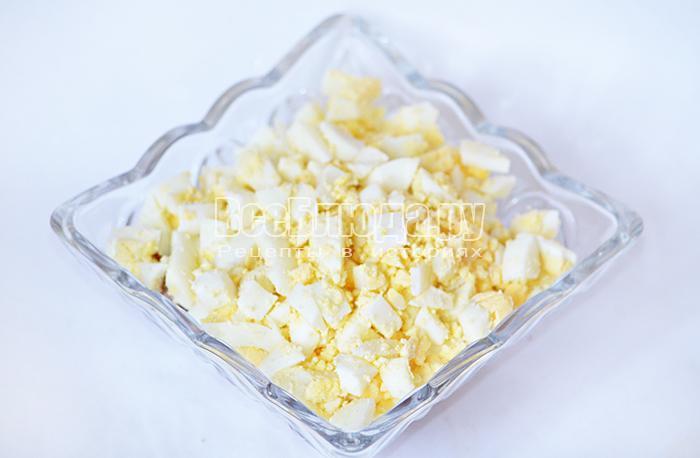 уложите лук и яйца, смазав слои