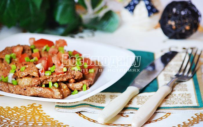 посыпьте мясо зеленью и нарезанным помидором