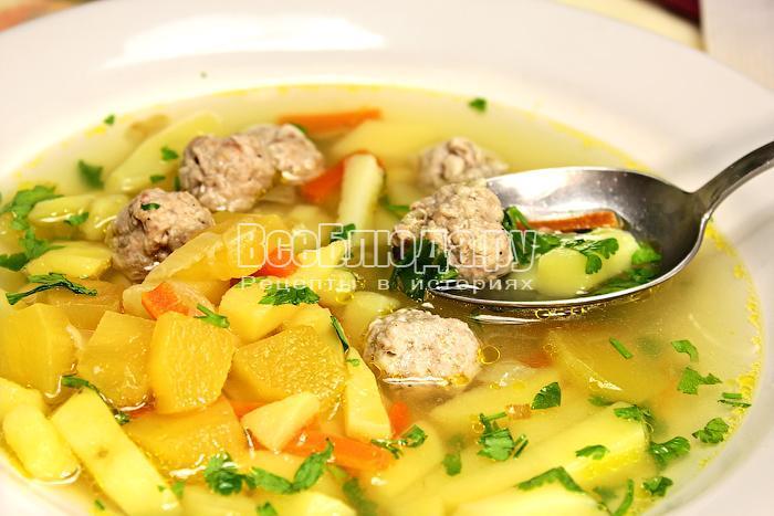 Суп в тарелке и ложка с супом