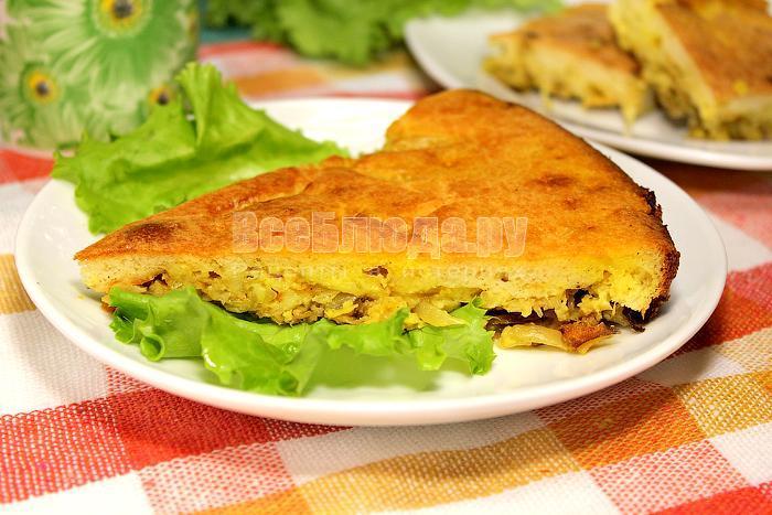 Кусочек готового капустного пирога на тарелке