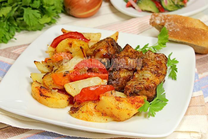 Готовые ребрышки с картофелем и овощами в духовке