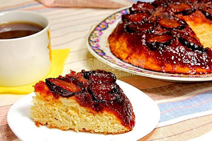 Кусочек готового перевернутого пирога со сливами